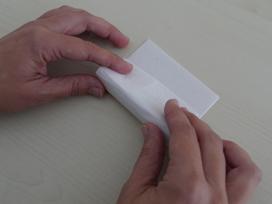 foto van wit velletje dat om het buisje gerold wordt